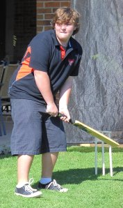 Cricketer holding bat waiting to hit the ball.