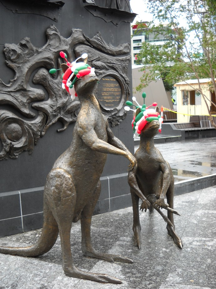 Statues of two kangaroos wearing red, white and green balloons on their heads.