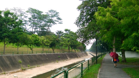 Concrete canal with trees on either side. On the right there is a path with a person holding an umbrella.