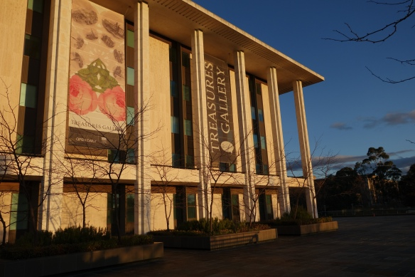 Western side of the library building with two large banners advertising the Treasures Gallery. Small deciduous trees with no leaves are in the foreground.