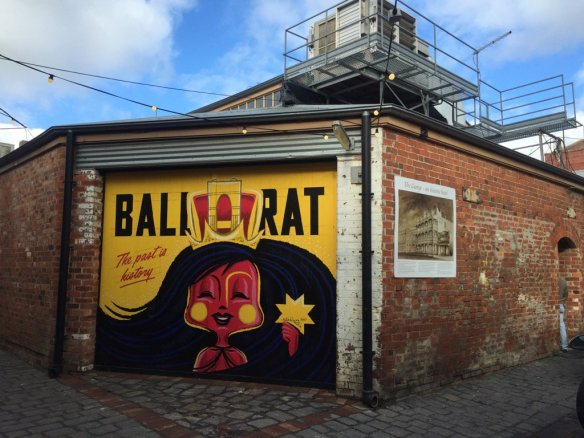"A mural on yellow background with red woman and black hair holding a yellow 7 pointed star. Ballarat with large black letters and ""The past is history"" in red underneath."