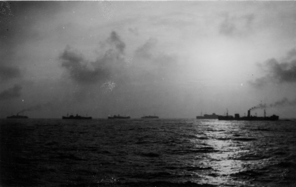 Cloudy sky and sea with 6 ships steaming forward